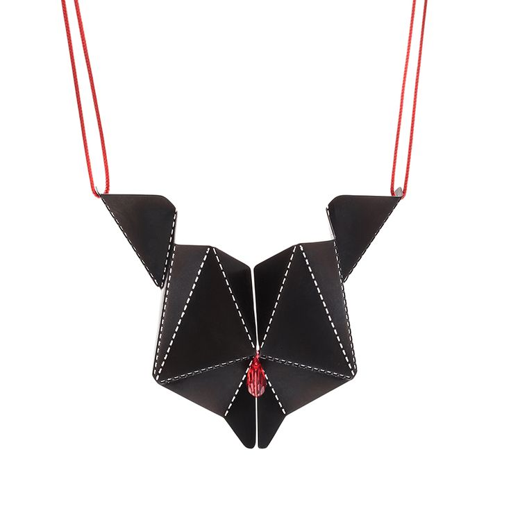 and crafted necklace made of black stainless steel with crystal, hanging on red tape.