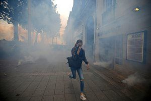 Nantes, France  A woman runs away from teargas during clashes with French riot police at another march demonstrating against labour law reforms