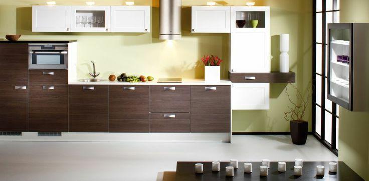 SOLUPPGÅNGENS KÖK    Minimalism är inte nödvändigtvis lika med anspråkslöshet. De mörkbruna luckorna i patinerad ekmelamin är kantade med eleganta aluminiumlister. Väggskåpens högblanka vitlackerade kasettspegelluckor bildar en smakfull kombination med de vita och svarta bänkskivorna.    Produkterna på bilden:  LUCKOR: TME40 Laminat, BrunPatineradEk / TMU13 MDF, Vit /  TMU13LA_TMU13KPOLA MDF, Vit, Klar glas  HANDTAG: UK020-21-096  BÄNKSKIVOR: TKM40 Laminat, Vit