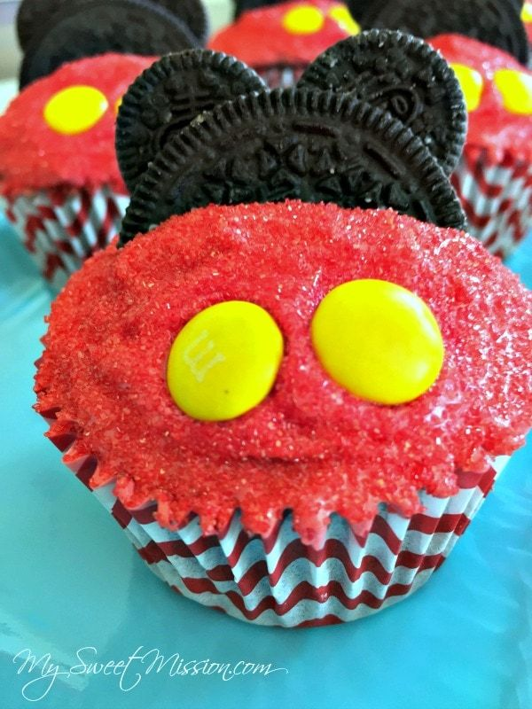 These Adorable Mickey Mouse Cupcakes are moist, with the creamiest buttercream frosting, a sprinkling of red sugar, and decorations to make them look like Mickey himself! #mickeymouse #cupcakes #chocolate #buttercream #desserts #kidsdesserts #partycupcakes #birthday
