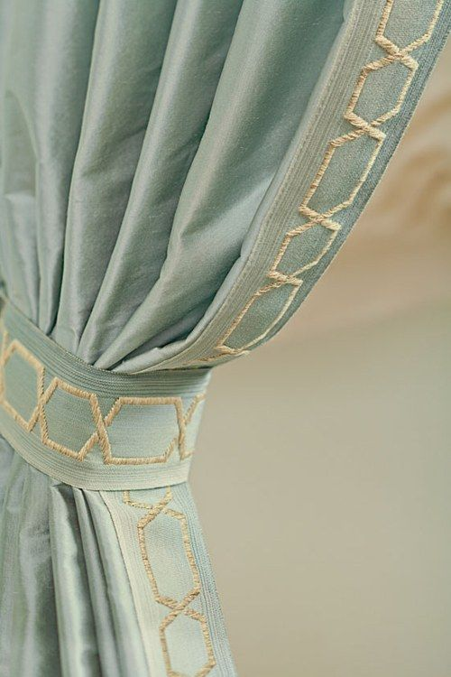 drapery panels with embroidered cross over band down the edge of panel & the matching fabric tie back has same embroidered design