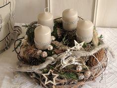 Aufwendig gestalteter Adventskranz bestehend aus einem grau gekälkten Rebenkranz und einem darauf sitzenden Mooskranz mit vier hell taupefarbenen Stumpenkerzen, welche mit Strassband umwickelt…