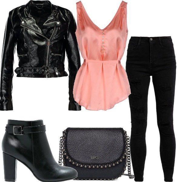 Giacca in fintapelle nera con chiusura in cerniera, canotta rosa in raso, jeans skinny a vita alta neri. Tronchetti neri in fintapelle, borsa a tracolla in fintapelle nera con profili borchiati.