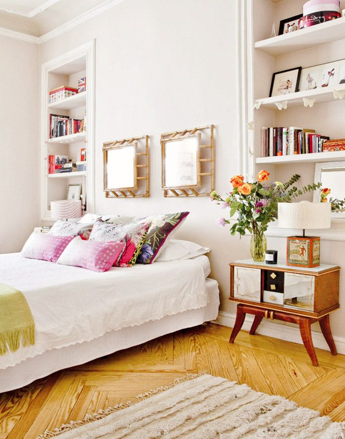 Feminine bedroom with built-in bookshelves and midcentury side table