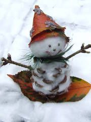 Snowman of pine cone, cotton wool, fall leaves and glitter