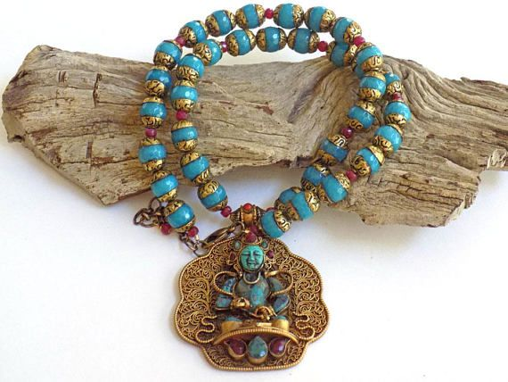 This exotic prayer bead necklace features a Tibetan brass prayer pendant. The Tibetan necklace is a one-of-a-kind statement piece. This turquoise bead necklace is 18 inches long but is adjustable with the addition of the 2 inch brass extension chain. The pendant necklace for women