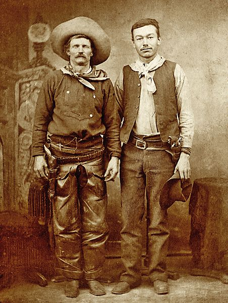 "The Genuine Cow Boy Captured Alive In this 1880s cabinet card, accurately captioned ""The Genuine Cow Boy Captured Alive,"" Cottonwood Charlie Nebo (far left), a proud proprietor of a horse ranch, wears a bib front shirt, shotgun chaps, bandanna, wide brimmed hat and his fringed, scabbard-style holster. His half-breed partner Nick has left off the chaps and boots, and is wearing a vest that was popular among frontier cowboys."