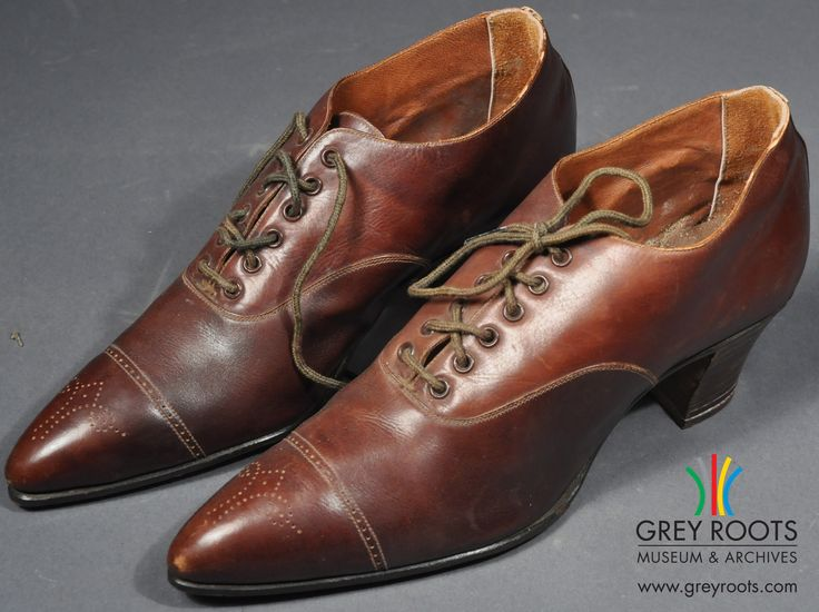 """A pair of ladies', brown leather, """"Model"""" brand shoes. They have a small, square heel and are lace-up. On each toe, there is a stylized flower design. Grey Roots Museum & Archives Collection."""