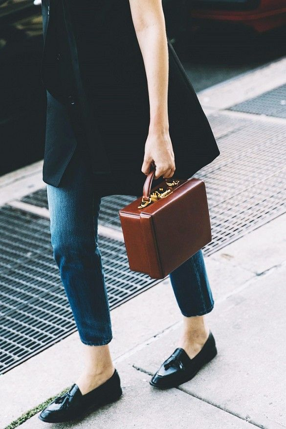 A Mark Cross box bag is paired with a long vest, jeans, and loafers