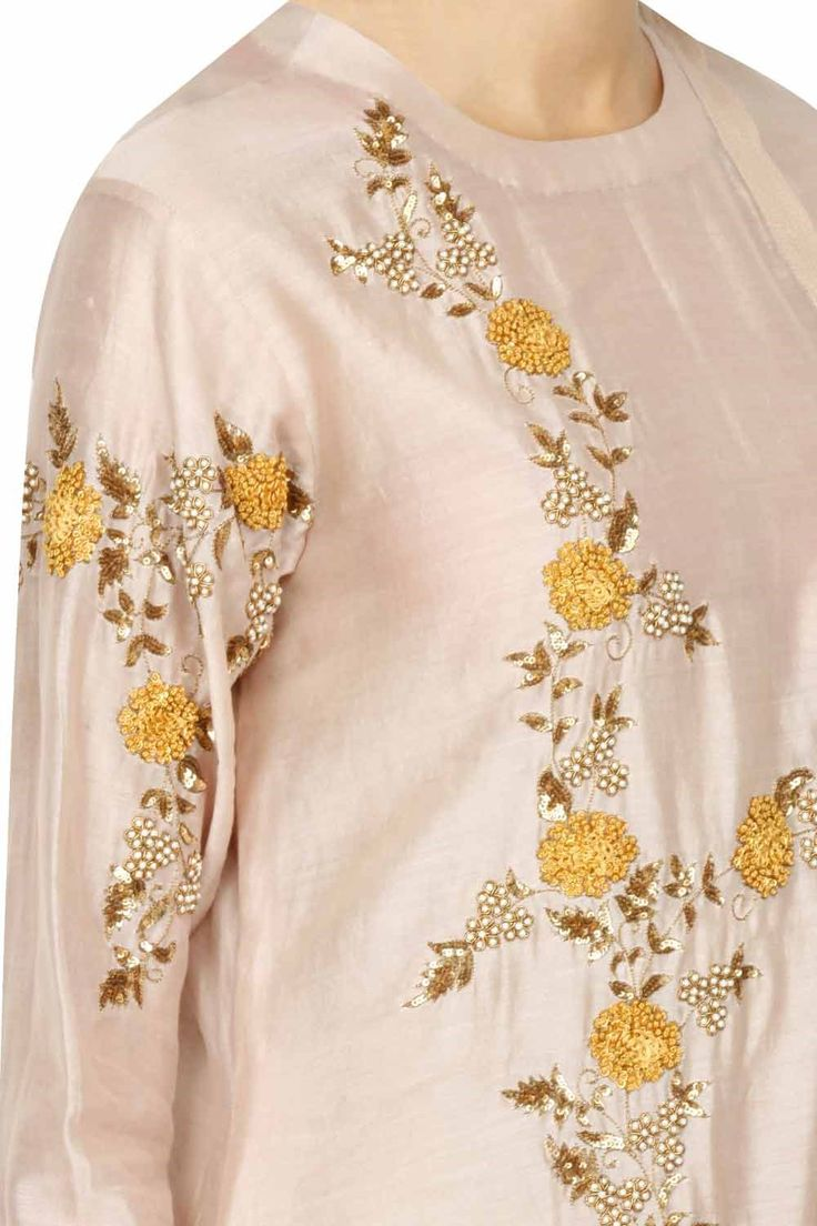 Featuring a blush kurta in chanderi base appliqued with gold sequins and flower pattern embroidery highlighted with beads and white pearl embellishment all over the front, back and sleeves. It has a button placket closure on the side front. It comes along with an off white brocade flared skirt and a scarf with floral embroidered motifs at the corner and gold zigzag border and thread latkans. Fabric: Chanderi silk, Chiffon, Brocade Care Instructions: Dry clean only.
