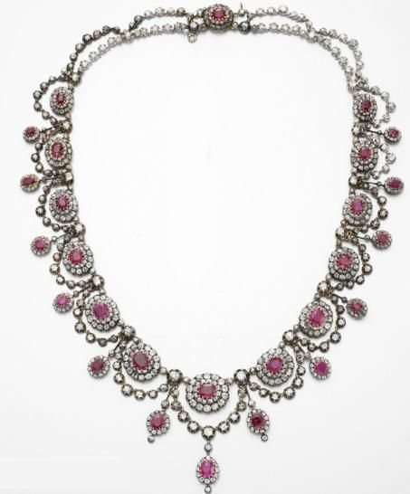 AN ANTIQUE RUBY AND DIAMOND NECKLACE. Designed as an old mine-cut diamond necklace of garland design, set with a graduated series of oval and cushion-cut rubies, each within an old mine-cut diamond surround, spaced by oval-cut ruby and old mine-cut diamond knife-edged links, mounted in silver-topped gold, circa 1880, 21 ins., with French assay marks