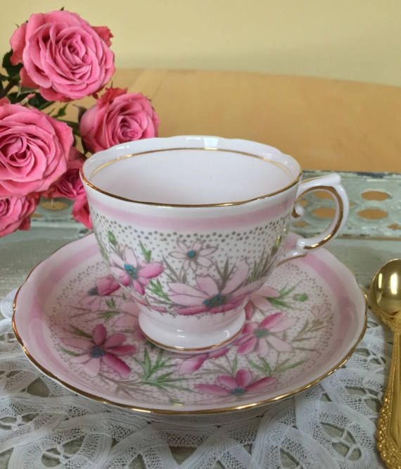 Vintage Tuscan footed teacup and saucer. A pink cup and saucer with pretty pink daisies or wildflowers with blue raised enamel centers. There is a pink band around the rims of the cup and saucer. Pattern number is 9494H. The pattern is also available in blue. Perfect for spring! Fine