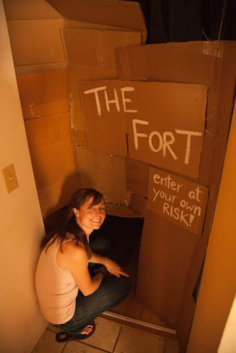 Adults build a cardboard fort in their home. How much fun is that!