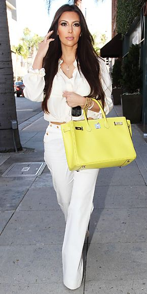 Kim Kardashian  WHAT SHE WORE  Kardashian dropped by the Vera Wang boutique in head-to-toe white accented with a neon Birkin bag.