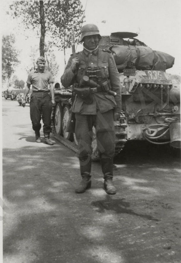 German soldier and a Pz. Kpfw. 38 (t) in the background, France 1940.