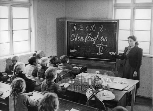 Deutschunterricht in einer Schule, 1944 Timeline Classics/Timeline Images #40er #schwarzweiß #Fotografie #photography #historisch #historical #traditional #traditionell #retro #nostalgic #Nostalgie #Schule #School #Schüler #Lernen #Studieren #Bildungseinrichtung #Unterricht #Schulzeit #Ausbildung #Lehrer #Mitschüler #Klassenzimmer #Schulbank #Frontalunterricht #Deutsch #Schreiben #Tafel