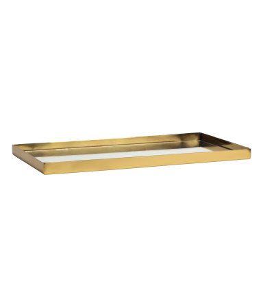 Guld. En rektangulär bricka i metall med låg kant. Brickan har botten i spegelglas. Storlek 1,5x13x26 cm.