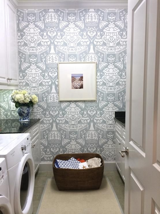 Beautiful laundry room features walls clad in David Hicks The Vase Wallpaper lined with white shaker cabinets suspended over a white front-load washer and dryer facing a folding station across from a bound diamond print sisal rug.