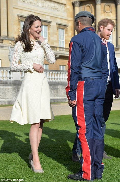 Catherine, Duchess of Cambridge meets a guest at a tea party in the grounds of Buckingham Palace to honour the children of those who have died serving in the armed forces
