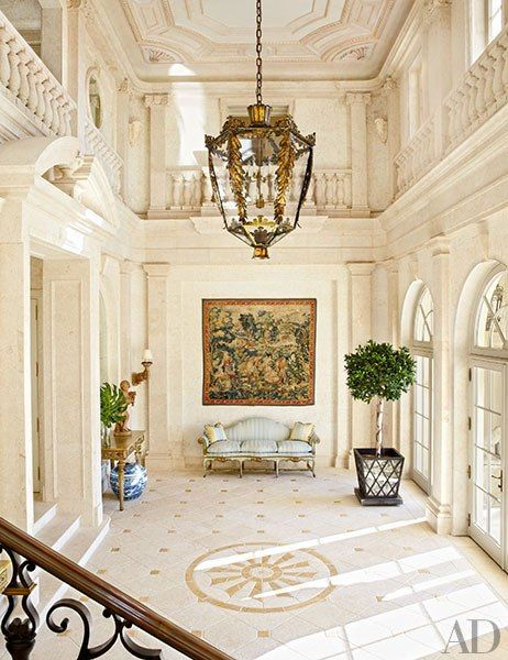 The entrance hall of Amado, a circa-1920 Palm Beach, Florida, mansion built by architect Addison Mizner and renovated by David Easton; the sconce is by Formations, the tapestry is 16th-century Flemish, and the planter at right is by Dennis & Leen.