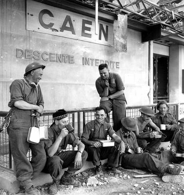 Canadian soldiers of the Dundas and Glengarry Highlanders regiment pause for lunch at the railway station of the French city of Caen.