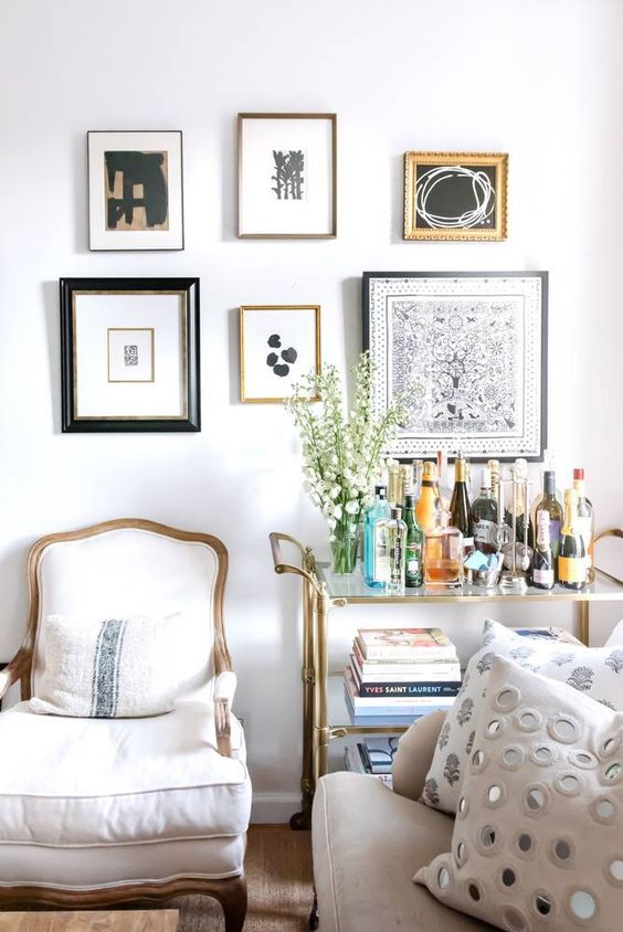 Gallery wall of small black and white artwork over a bar cart in a neutral living room design with a white, beige, and brass (gold) color scheme - domino.com