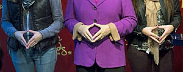 Her political fortunes may wax and wane but here tourists imitate the trademark rhombus hand gesture of German Chancellor Angela Merkel as they stand next to her new wax figure at the Madame Tussauds wax museum in Berlin. (Thomas Peter / Reuters)