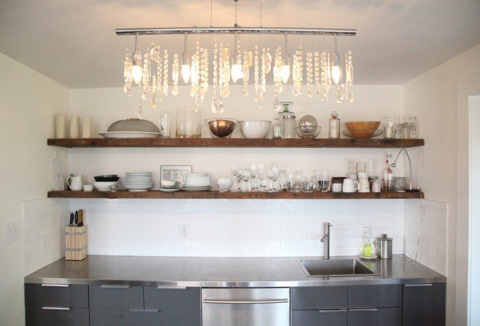 Beautiful small kitchen with classic chandelier, modern kitchen appliances and rustic shelves