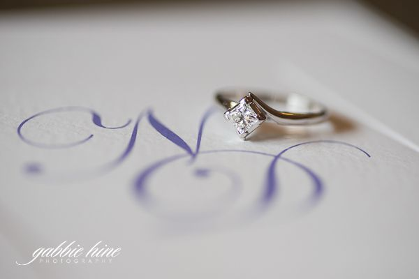 The bride's stunning engagement ring placed on the entwined initials of their names