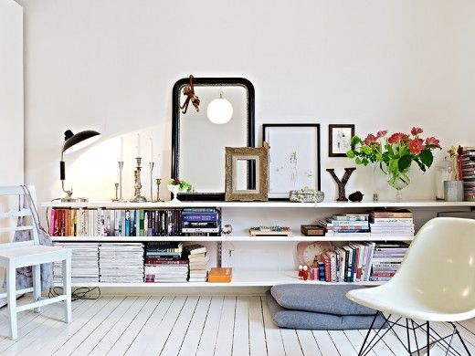 The low & long shelving provides room for storage and display.  I love the balance and low of the placement of mirrors & frames.  The overall look is curated, but not inaccessible.