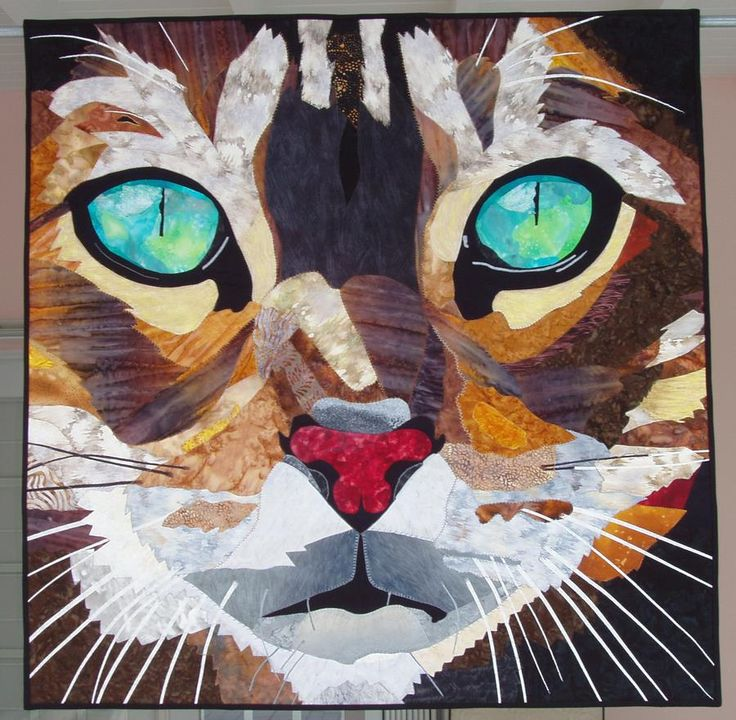 """""""Emerald Eyes"""" by Elizabeth Janowitz from Pinecrest, FL, is an original design. Fused appliqué, thread painting, and fabric painting techniques were used. It is based on the Firekat photograph by Darren Levant and is machine quilted. (Ref. quilterbeth.blogs...)"""