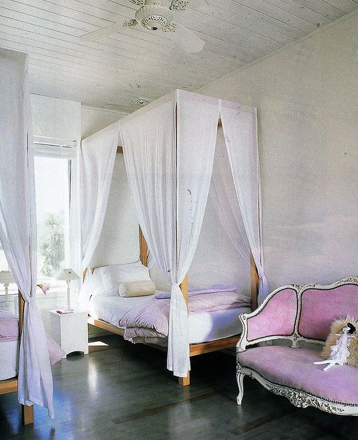 For the Young Lady. A modern four poster with an antique pink upholstered settee. Interior Designer: unknown.