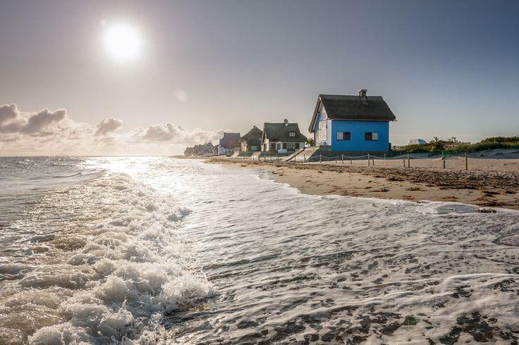 Die kleinen Strandhäuser stehen im Licht des Sonnenaufgangs am Strand in Heiligenhafen, einer der beliebtesten Ausflugsziele Schleswig-Holsteins.