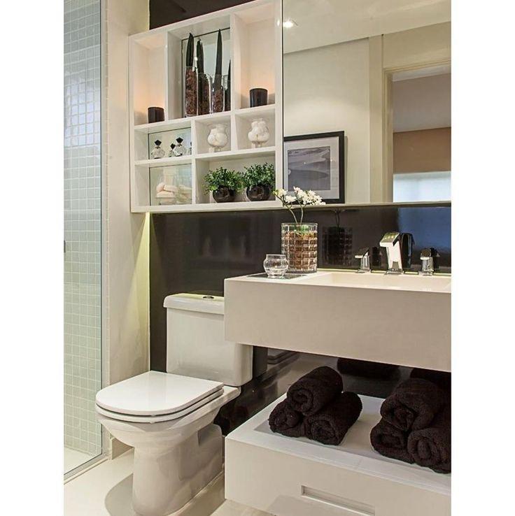 """Lavabo """"black and white"""". O revestimento na cor preta destacou a bancada e os armários com nichos e espelho. Sob a bancada, um gaveteiro móvel serve de apoio para toalhas."""