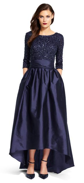 Sequins alight a three quarter sleeve bodice that gives way to a high low taffeta ball skirt.