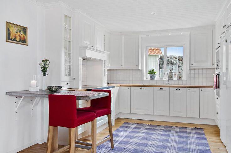 Köket är smakfullt inrett med vita luckor och vitrinskåp med belysning.