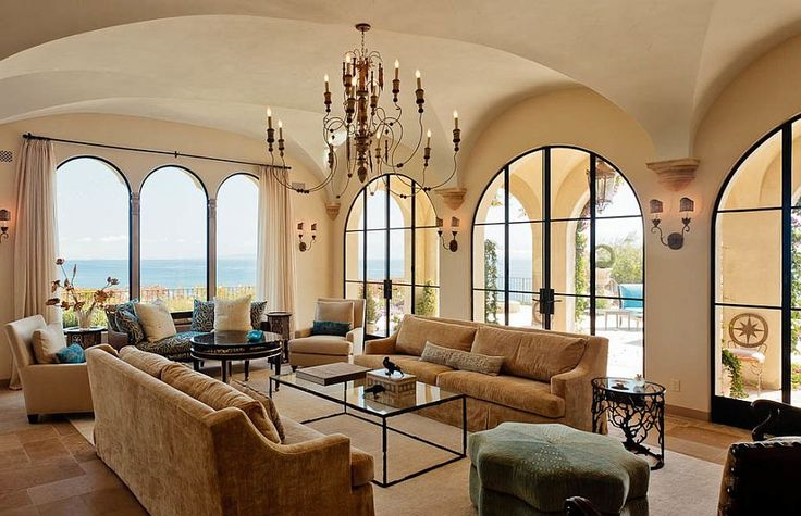 Arched windows and limestone-inspired paint give the living room a modern Mediterranean style