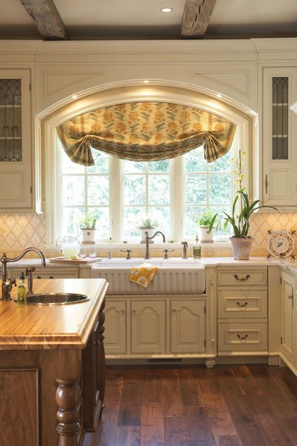 """Arched Roman Shade    The perfect solution for an arched window is an arched Roman shade. The internal mechanics (rings) are inset far from the edges to create """"tails"""" for high visual interest on the sides.    Style tip: Coordinate the fabric for the kitchen window treatment with the colors and design of your backsplash. It's a great way to create design cohesion."""