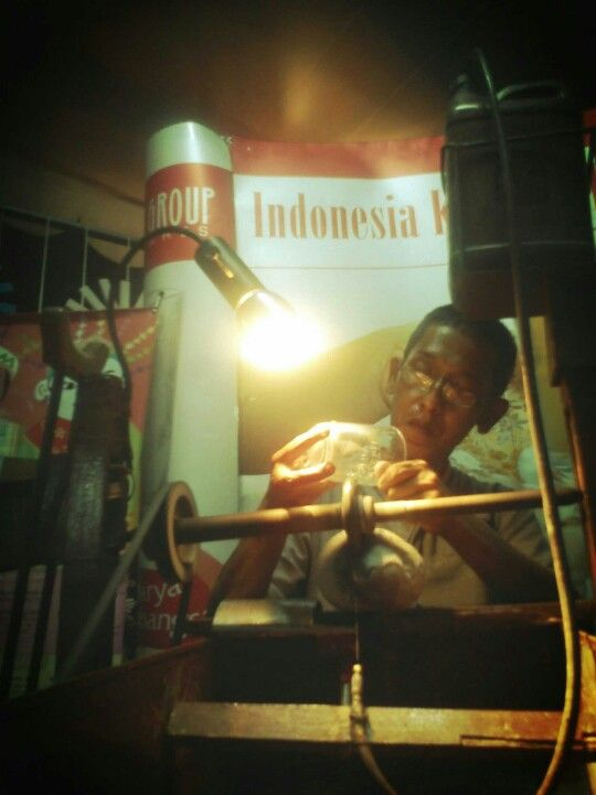 An artist from Central Java, redecorating a glass with his traditional utensils.