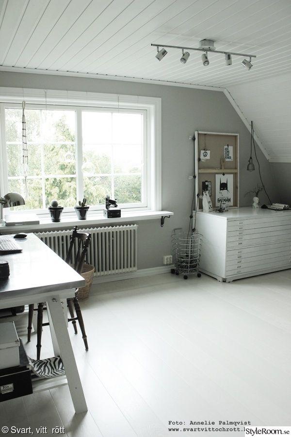 arbetsrum,ateljé,skrivbord,hemmakontor,stålkorg,ljusslinga,arkivskåp,stort fönster,ljusinsläpp,vit pakett,vitt golv,konsttryck,tavlor,posters,batman,batmantavla