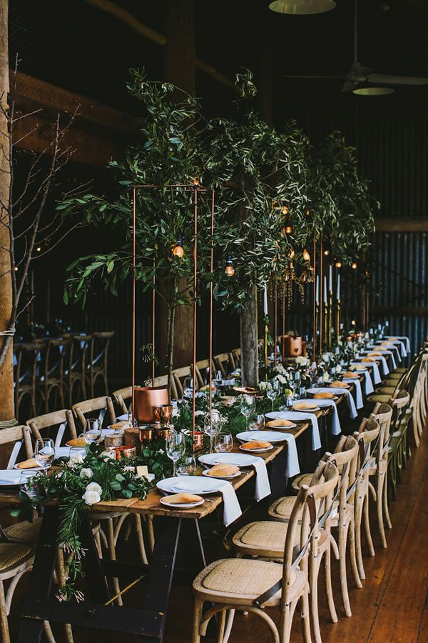Beautiful long farm table setting with loads of greenery and details! indoor garden reception - photo by Lara Hotz Photography http://ruffledblog.com/botanical-australian-barn-wedding
