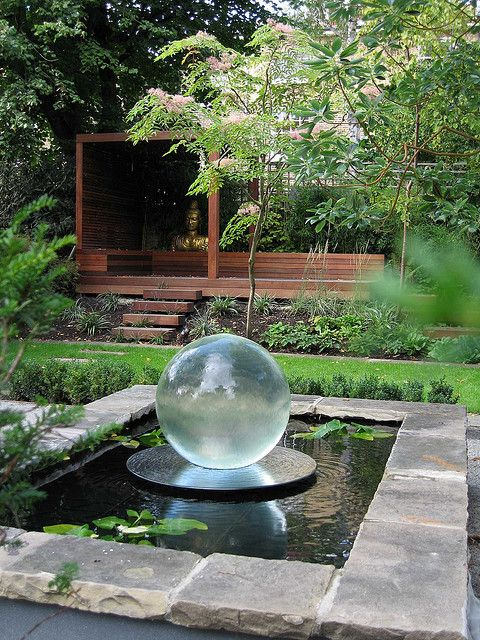 a spherical glass water feature in a raised pool is the center piece of this garden