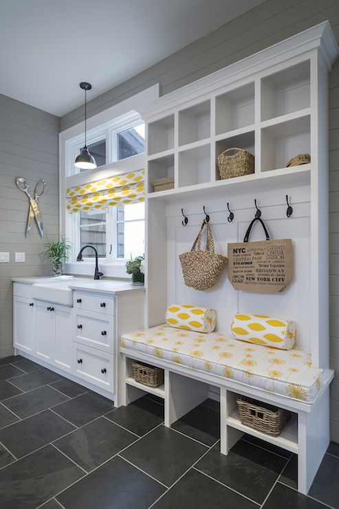 Yellow and gray mud room features gray shiplap clad walls adorned with an oversize pair of scissors alongside shaker cabinets which frame a farmhouse sink and oil-rubbed bronze faucet atop light gray counters situated below a large window dressed in a yellow ikat roman shade lit by an oil-rubbed bronze pendant.