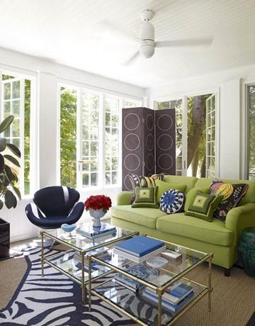 Green & blue eclectic living room design with french windows, green sofa with geometric pillows, gold faux bamboo glass top coffee tables, navy blue & white cowhide zebra rug, sisal rug, purple circles floor screen, green garden stool and white walls paint color. white gold green blue, purple living room colors.  http://www.decorpad.com/photo.htm?photoId=39909=3=2=88853