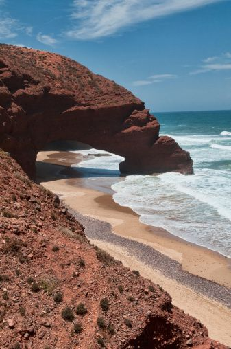 Natural stone arch along beach at Legzira Plage near Sidi Ifni, Morocco.