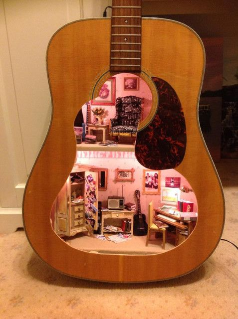 A Dollhouse Built Inside of an Acoustic Guitar.  Lorraine Robinson of Fairy Meadow Miniatures in Australia created this beautiful dollhouse inside of an acoustic guitar as a thoughtful birthday gift for daughter Cathryn who is headed off to university. It was made using Cathryn's first guitar.
