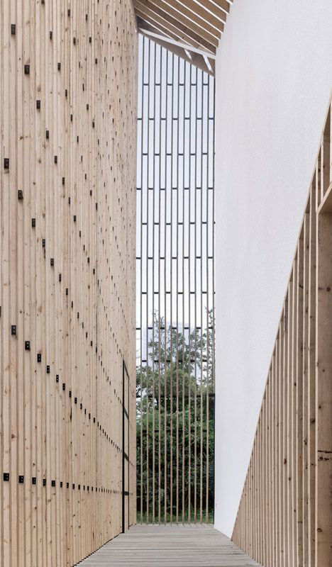 Chapel with double-layered facade, consisting of solid white walls screened behind a semi-transparent wooden skin