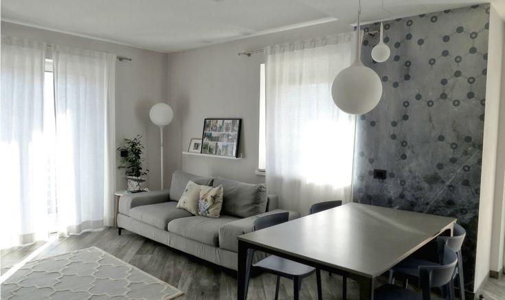 Il progetto completo di soggiorno con cucina a vista. Colori blu e grigio in salotto e toni neutri nella cucina a vista.