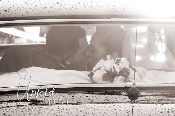 Bride and Groom share a secret kiss ~ romantic. Seated in the back seat of their vintage wedding car. Image by Upfold Photography, Auckland.
