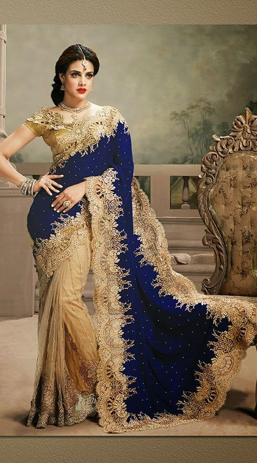 Woman looks more beautiful like designer sarees! Get the dazzling look draped in this cream and royal blue half velvet and half net saree. This pretty attire is crafted with a rich work of zari, resham, embroidery and lace. This sari is completed with a matching blouse piece. The blouse of this saree can be stitched in the maximum bust size of 42 inches.
